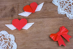 Coeurs d'origami avec des ailes sur un fond en bois avec la dentelle Deux coeurs Photographie stock