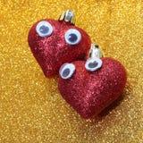 Coeurs dans l'amour avec des yeux à l'arrière-plan d'or Photos stock