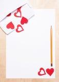 Coeurs dans l'enveloppe, le papier et le crayon Photographie stock libre de droits