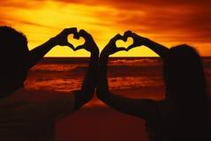 Coeurs de bâtiment de couples d'amour dans le coucher du soleil Images libres de droits