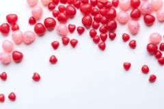 Coeurs de cannelle et dragées à la gelée de sucre rouges et roses sur le fond blanc image stock