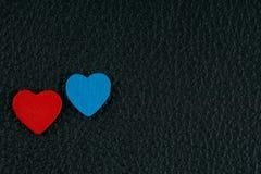 Coeurs de carte de jour du ` s de Valentine, rouges et bleus sur le cuir noir Photos stock