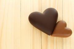 Coeurs de chocolat à noir et à lait sur le fond en bois Images libres de droits