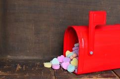 Coeurs de conversation de sucrerie se renversant hors d'une boîte aux lettres rouge Photographie stock libre de droits
