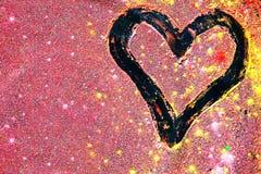 Coeurs de dessin dans le mélange des poudres colorées Photo stock