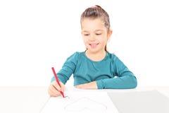 Coeurs de dessin de petite fille à un morceau de papier vide Photo stock