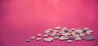Coeurs de feutre de pourpre et de blanc sur un fond de roses indien avec la lumière chaude - valentines, amour Photos libres de droits