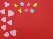 Coeurs de feutre sur le fond rouge avec amour que vous textotez Images stock