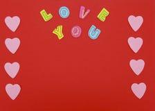 Coeurs de feutre sur le fond rouge avec amour que vous textotez Photographie stock