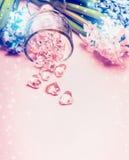 Coeurs de fleur de jacinthes et en verre sur le fond rose-clair Photo stock