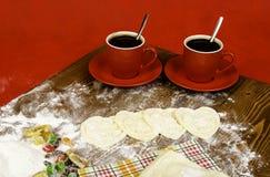 Coeurs de pâte, de tasse de café de deux rouges et de fruits secs Images libres de droits