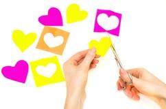 Coeurs de papier coupés par mains femelles Photo stock
