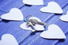 Coeurs de papier et clés argentées sur le fond en bois pourpre Photos libres de droits