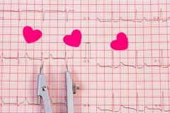 Coeurs de papier et de calibres sur le graphique d'électrocardiogramme, la médecine et le concept de soins de santé Images stock