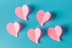 Coeurs de papier roses d'isolement sur le fond bleu, symbole de l'amour dessus Photographie stock