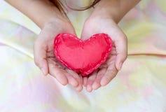 Coeurs de papier rouges en gros plan sur les mains des femmes Photographie stock libre de droits