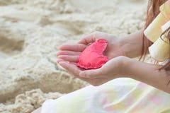 Coeurs de papier rouges en gros plan sur les mains des femmes Symbole de l'amour Photos stock