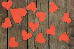 Coeurs de papier rouges sur le vieux fond en bois Photos stock