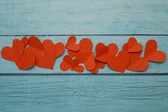 Coeurs de papier rouges sur un fond en bois bleu images stock