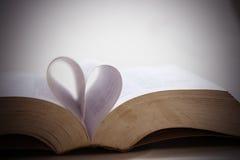 Coeurs de papier sur le vieux livre pour le jour du ` s de Valentine Image libre de droits