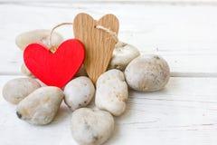 Coeurs de Saint-Valentin sur les roches et le fond en bois Image libre de droits