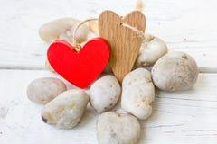 Coeurs de Saint-Valentin sur les roches et le fond en bois Photographie stock