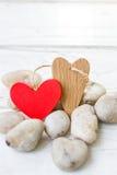 Coeurs de Saint-Valentin sur les roches et le fond en bois Images stock