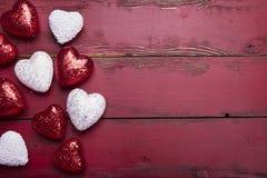 Coeurs de scintillement de rouge et de blanc sur un fond en bois rouge Image stock