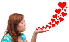 Coeurs de soufflement de jeune femme Image stock
