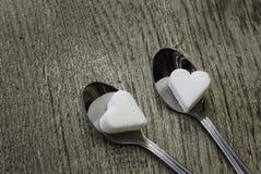 Coeurs de sucre blanc avec deux cuillères de thé sur le fond en bois Image libre de droits