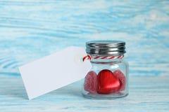 Coeurs de sucrerie dans un pot en verre avec l'étiquette Photos stock