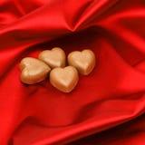 Coeurs de sucrerie sur le satin rouge Images stock