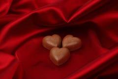 Coeurs de sucrerie sur le satin rouge Images libres de droits