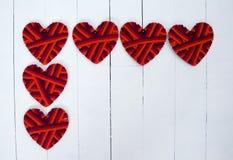 Coeurs de textile de feutre sur un fond en bois blanc Photos stock