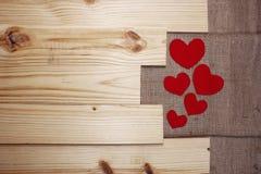 Coeurs de thème de valentines sur le fond et la toile de jute en bois image libre de droits