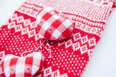 Coeurs de tissu sur une écharpe rouge Images stock