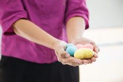 Coeurs de tricotage multicolores colorés de foyer sélectif tenus par les deux mains de la femelle, représentant des coups de main image stock