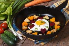 Coeurs des carottes, des pommes de terre, des betteraves et des oeufs dans une poêle Image libre de droits