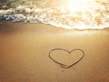 Coeurs dessinés sur le sable d'une plage images stock