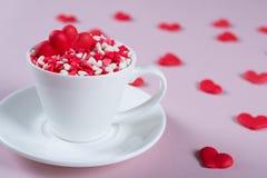 Coeurs doux rouges de sucrerie de sucre dans une tasse de café Concept de jour du ` s d'amour et de Valentine Photos stock