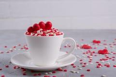 Coeurs doux rouges de sucrerie de sucre dans une tasse de café Décoration de concept de jour du ` s d'amour et de Valentine Photographie stock