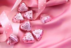 Coeurs du chocolat de Valentine sur le satin rose Image stock