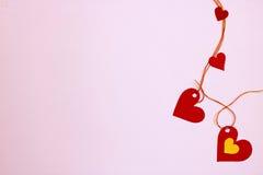 Coeurs du papier - verticalement relié, sur un fond rose doux Photo stock