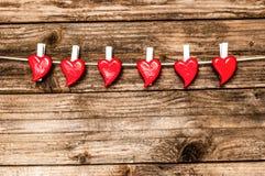 Coeurs du ` s de Valentine accrochant au-dessus du fond en bois grunge Image libre de droits