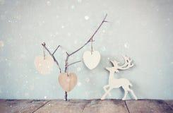 Coeurs en bois accrochants plus d'et décoration en bois de cerfs communs de pluie au-dessus de fond en bois rétro image filtrée Photographie stock libre de droits
