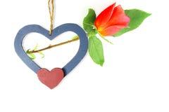 Coeurs en bois avec la rose de rouge à l'arrière-plan blanc Photo libre de droits