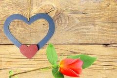 Coeurs en bois avec la rose de rouge au vieil arrière-plan en bois Photos libres de droits