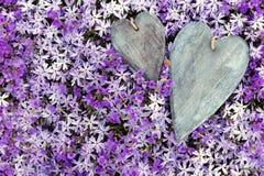 Coeurs en bois de la carte de voeux deux placé sur beaucoup de fleurs Photos libres de droits