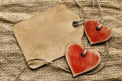 Coeurs en bois et feuille de papier sur le fond de tissu Image stock