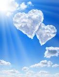 Coeurs en nuages contre un ciel propre bleu Photo stock